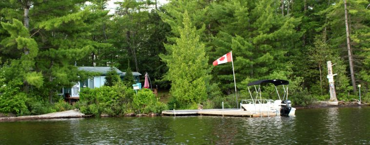 image: cottage shoreline, dock with Canada flag